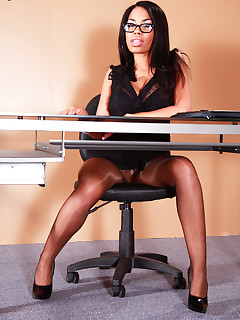 Ebony secretary in brown pantyhose posing at the office.