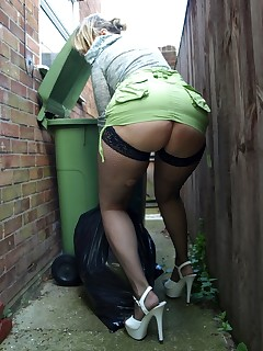 Dirty English housewife takes out the trash in her fishnet stockings.